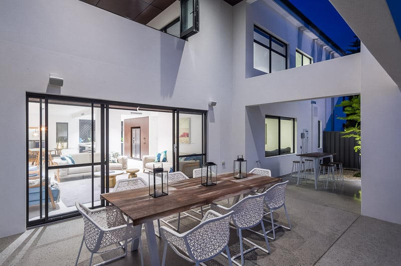 outdoor seating area backlit by a modern kitchen